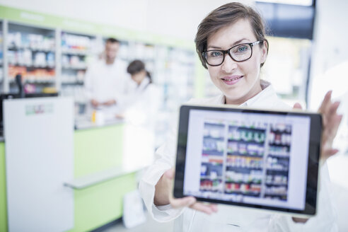Portrait of smiling pharmacist in pharmacy showing tablet - WESTF23993