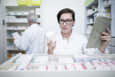 Pharmacist with tablet and medicine at cabinet in pharmacy - WESTF23996