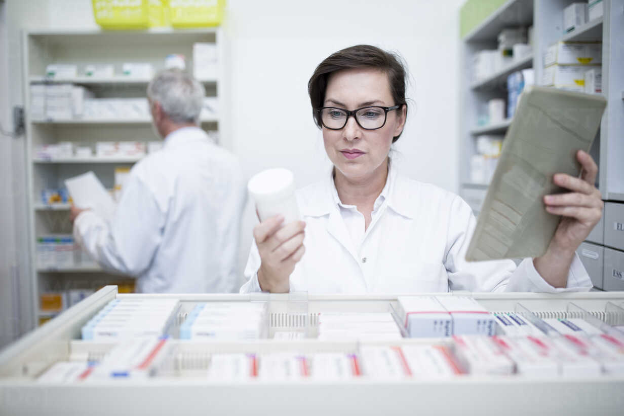 Pharmacist with tablet and medicine at cabinet in pharmacy - WESTF23996 - Fotoagentur WESTEND61/Westend61