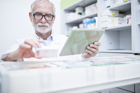 Pharmacist with tablet and medicine at cabinet in pharmacy - WESTF24002