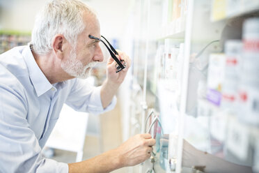 Mature man looking at cabinet with medicine in pharmacy - WESTF24005
