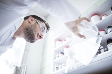 Man working in laboratory of a pharmacy - WESTF24014