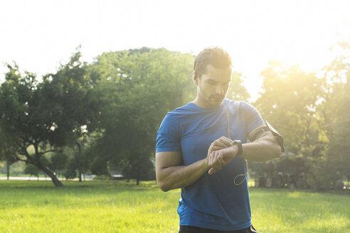Runner in urban park checking his smartwatch - SBOF01108
