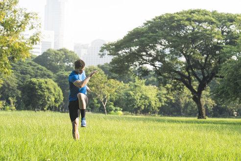 Runner warming up in urban park - SBOF01111