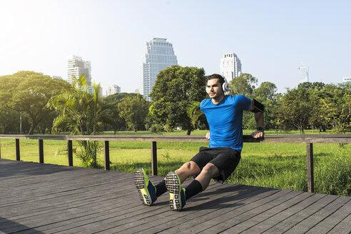 Runner with headphones doing push-ups in urban park - SBOF01123