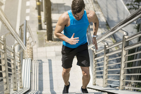 Man in blue fitness shirt running upstairs in city - SBOF01126