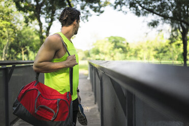 Runner standing on bridge in park, carrying bag and shoes - SBOF01135