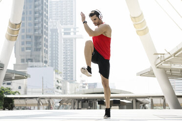 Man in red fitness shirt warming up in city - SBOF01147