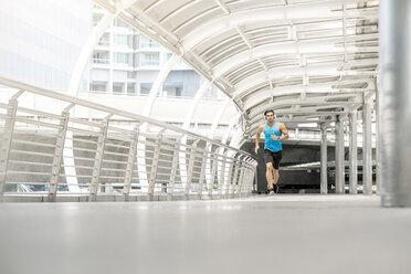 Fit man running on a bridge in the city - SBOF01159