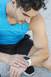 Athlete sitting on the ground, checking his smartwatch - SBOF01165