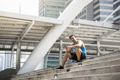 Runner wearing earphones, checking messages on his smartphone - SBOF01168
