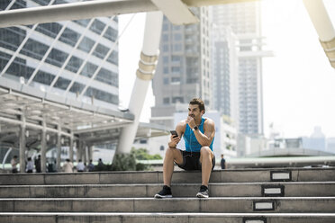 Runner wearing earphones, checking messages on his smartphone - SBOF01171