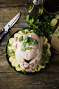 Uncooked chicken with parsley and potatoes in baking pan - GIOF03731