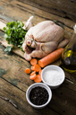 Raw chicken with carrots, parsley, garlic, pepper and salt on a chopping board - GIOF03737