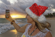 Carribean, Dominican Republic, Punta Cana, woman with Christmas cap taking selfie on the beach - GFF01053