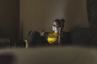 Woman with headphones listening to music on couch at home - UUF12511