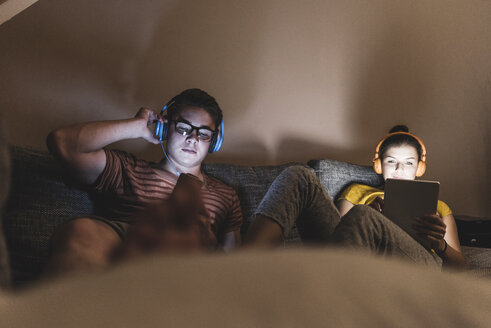 Couple with headphones relaxing on couch at home - UUF12517