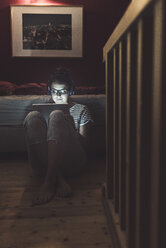 Woman with headphones and tablet sitting on the floor at home - UUF12529