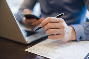 Man at desk using cell phone and holding ball pen in his hand, close-up - DIGF03220