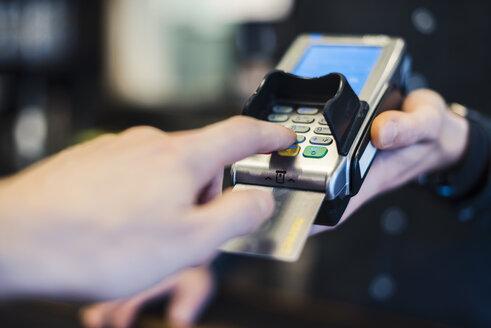 Man using credit card reader, close-up - DIGF03223