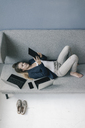 Businesswoman lying on the couch with several electronic devices using tablet - JOSF02098
