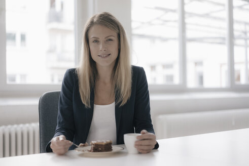 Portrait of smiling businesswoman having coffee and cake at desk in the office - JOSF02101