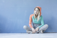 Portrait of smiling woman wearing hooded jacket sitting on the floor in front of blue wall - JOSF02107