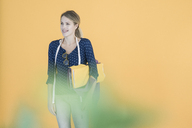 Portrait of smiling fashion designer in front of yellow wall - JOSF02119