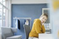 Portrait of fashion designer sitting at desk in her studio - JOSF02122