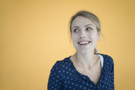 Portrait of laughing woman in front of yellow wall - JOSF02131