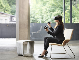 Businesswoman wearing VR glasses sitting on chair - CVF00015