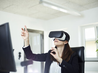 Businesswoman wearing VR glasses in office - CVF00018
