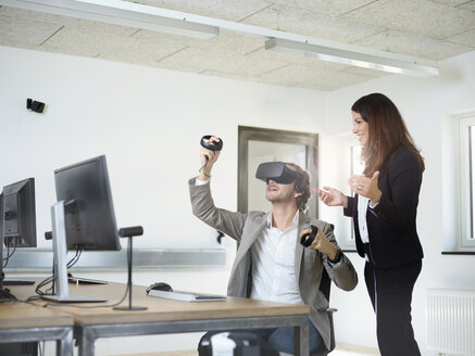 Woman with man wearing VR glasses in office - CVF00021