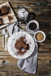 Bitten brownie on plate and cup of coffee - GIOF03756