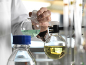 Scientist holding flask during an experiment in the laboratory - ABRF00009