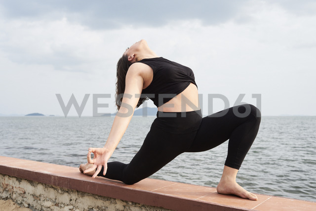 Young woman practicing yoga on a wall by the sea - IGGF00388