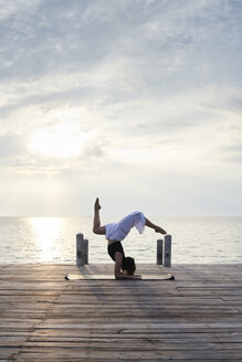 Young woman practicing yoga on a jetty by the sea at sunset - IGGF00391