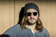 Portrait of bearded man with long hair wearing sunglasses and wooly hat - FMKF04680