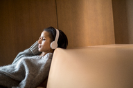 Portrait of relaxed young woman listening music with headphones on couch - FMKF04686