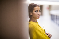 Portrait of woman wearing yellow pullover leaning against wall - FMKF04704