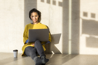 Portrait of smiling young woman sitting on the floor using laptop - FMKF04713