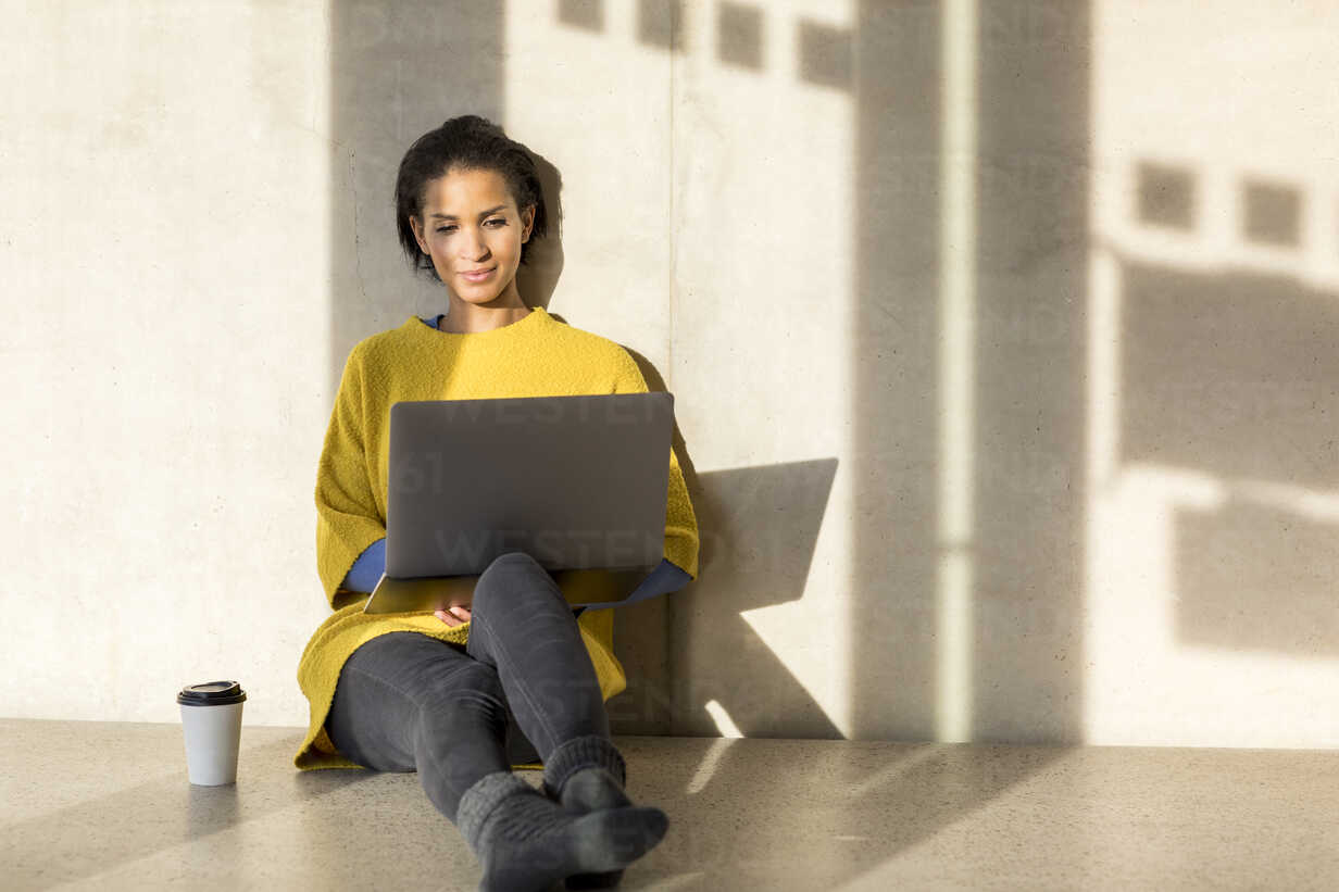 Portrait of smiling young woman sitting on the floor using laptop - FMKF04713 - Jo Kirchherr/Westend61