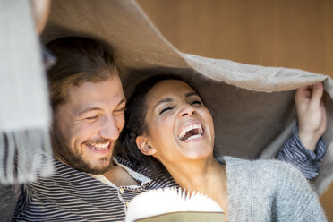 Portrait of laughing young couple at home - FMKF04722