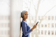 Portrait of young woman with cell phone in front of window - FMKF04728