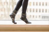 Woman wearing knitted socks balancing on window sill, partial view - FMKF04731