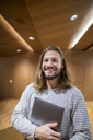 Portrait of laughing man with laptop in university - FMKF04740