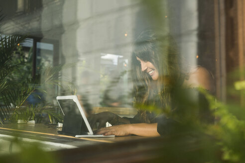 Smiling woman using tablet in a cafe behind window - SBOF01176