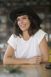 Portrait of smiling woman with hat in a cafe - SBOF01188