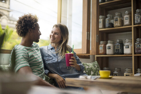 Smiling couple sitting in cozy cafe in front of window - SBOF01191