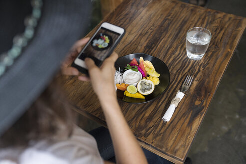 Woman taking a picture of food on a plate with smartphone - SBOF01194